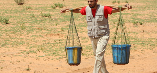Zaid Alrawni carries heavy buckets from the oasis to a village in Niger, the strain of the heavy weight visible on his face.