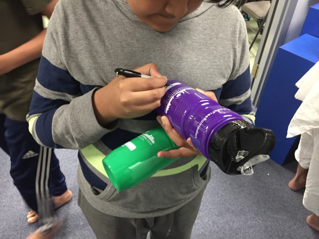 A boy writes his name on a ramadan bottle-Photo credit: Toronto Muslims